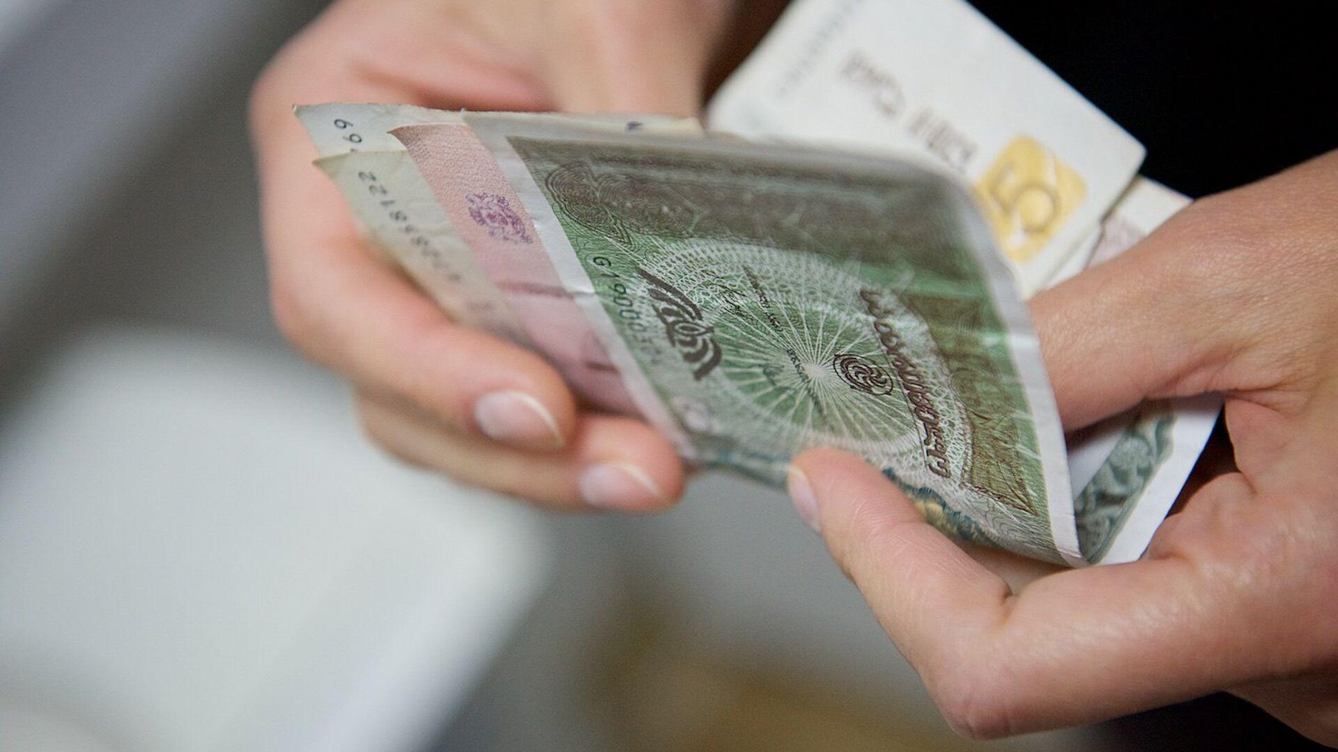 Человек держит в руках купюры грузинской валюты лари различного номинала - Sputnik Грузия, 1920, 06.10.2021