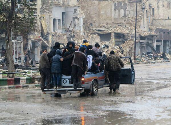 Жители восточного Алеппо едут по одному из городских кварталов после его освобождения от боевиков - Sputnik Грузия