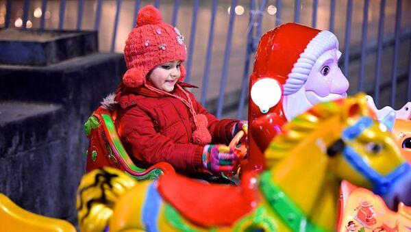 Ребенок на новогодней карусели у елки на проспекте Руставели в центре грузинской столицы - Sputnik Грузия