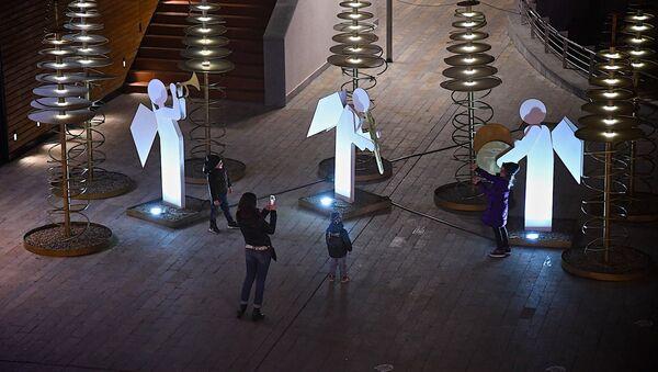Новый год и Рождество - люди фотографируются в праздничные дни рядом с фигурами ангелов в одном из тбилисских торговых центров - Sputnik Грузия