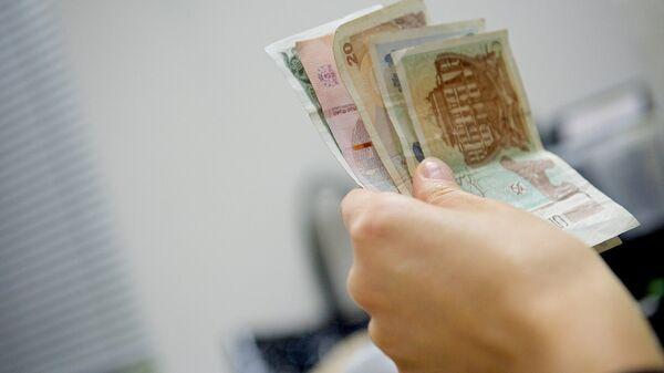 Человек держит в руках купюры грузинской валюты лари различного номинала - Sputnik Грузия