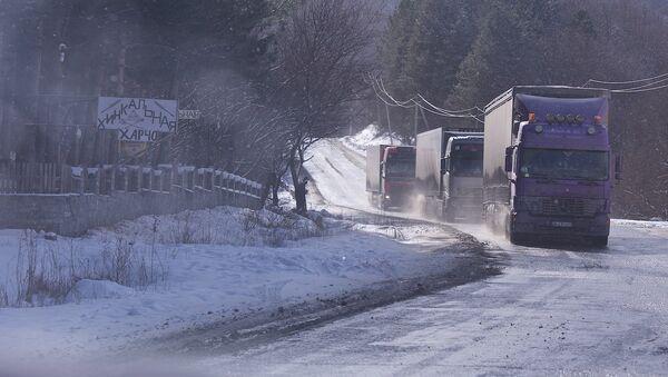 Грузовые трейлеры едут по дороге зимой в горах - Sputnik Грузия