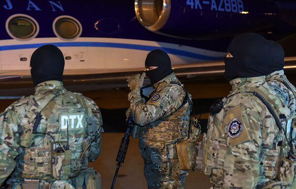 Сотрудники Государственной службы безопасности Азербайджана встречают в аэропорту самолет, доставивший блогера Александра Лапшина - Sputnik Грузия