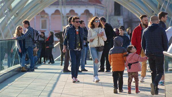 Жители и гости грузинской столицы гуляют весенним днем по мосту Мира в центре Тбилиси - Sputnik Грузия