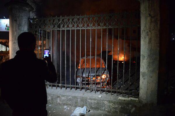 Человек фотографирует на смартфон сожженные в ходе беспорядков в Батуми машины - Sputnik Грузия