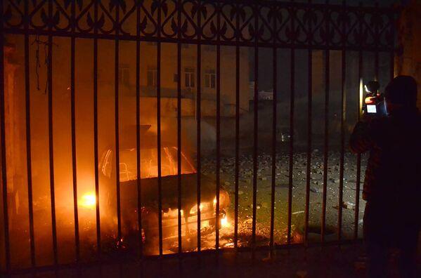 Оператор одного из грузинских телеканалов снимает сожженную в ходе беспорядков в Батуми машину - Sputnik Грузия