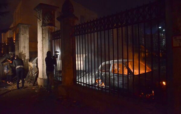 Оператор одного из грузинских телеканалов снимает сожженные в ходе беспорядков в Батуми машины - Sputnik Грузия