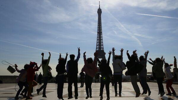 Туристы позируют для фото на фоне Эйфелевой башни в солнечный день в Париже - Sputnik Грузия