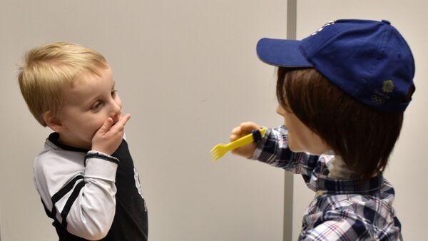 Пятилетний Харрисон, который болен аутизмом, играет с Каспаром, человекоподобным роботом, разработанным в университете Хартфордшира для взаимодействия и улучшения жизни детей с аутизмом в Стивенедж, Британия - Sputnik Грузия