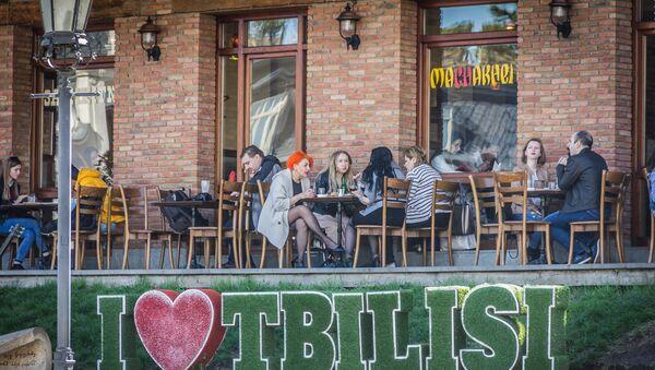 Посетители кафе сидят за столиками на улице - Sputnik Грузия