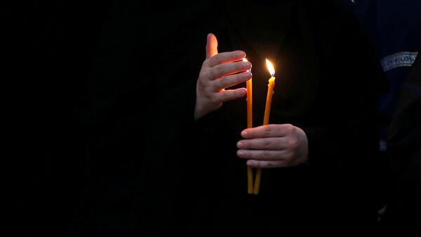 Монахиня держит зажженную свечу во время праздничной Пасхальной службы в Кафедральном соборе Святой Троицы Самеба - Sputnik Грузия