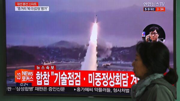 Женщина проходит мимо телевизионного экрана, показывающего видеозапись запуска ракеты Северной Кореей, на железнодорожной станции в Сеуле - Sputnik Грузия