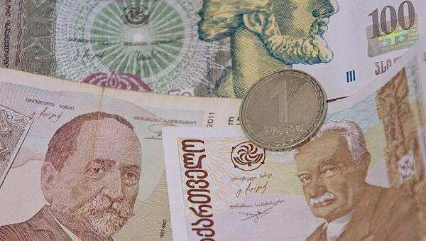 Монета достоинством в 1 лари на банковских купюрах различного номинала - Sputnik Грузия