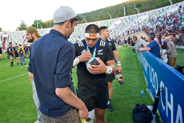 Капитан сборной Новой Зеландии по регби U20 подписывает на память мяч для игры в регби одному из грузинских болельщиков - Sputnik Грузия