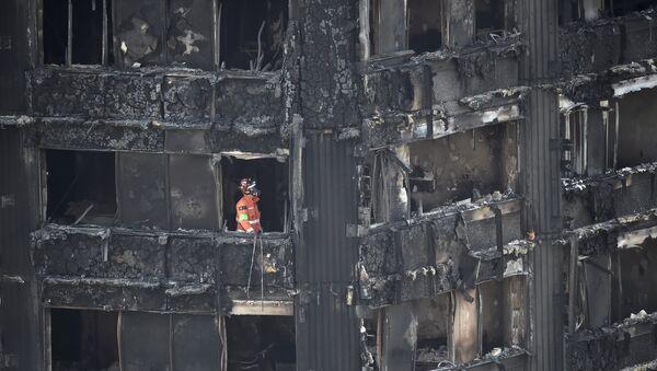 Один из сотрудников службы спасения работает на месте пожара в многоэтажном жилом доме в Лондоне - Sputnik Грузия