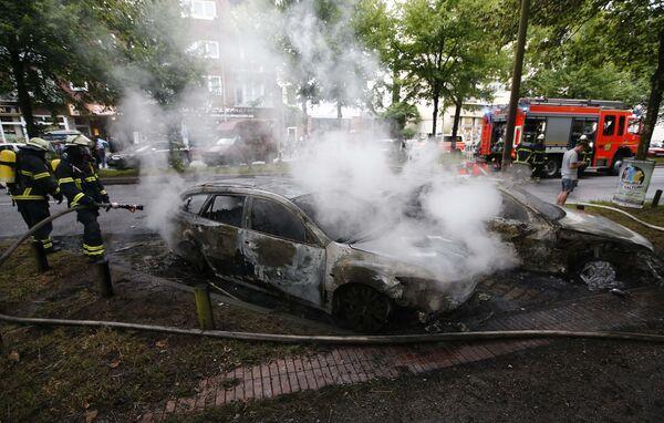 Пожарные работают на месте, где в результате беспорядков во время демонстраций против G20 в Гамбурге сгорели ряд автомобилей - Sputnik Грузия