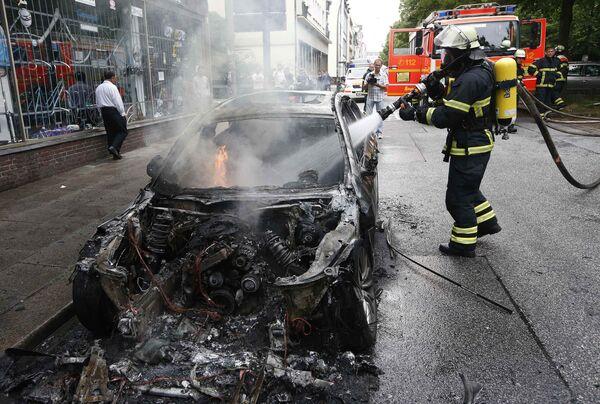 Пожарный тушит машину, сожженную в ходе акций протеста в Гамбурге против саммита G20 - Sputnik Грузия