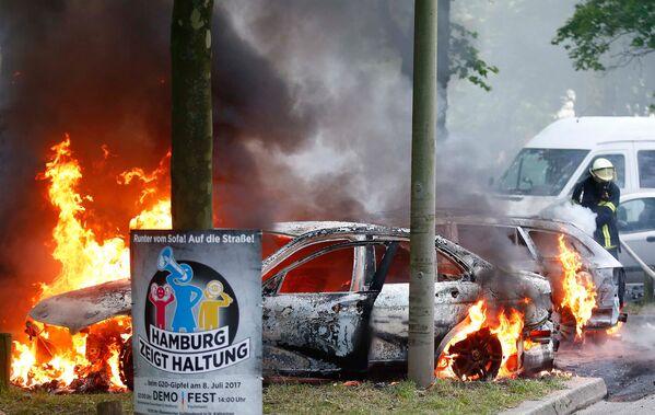 Пожарные сражаются с огнем на месте, где были подожжены несколько автомобилей во время акций протеста против саммита G20 в Гамбурге - Sputnik Грузия