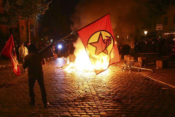 Один из протестующих у горящей баррикады - так ночью в Гамбурге проходили акции протеста против саммита G20 - Sputnik Грузия