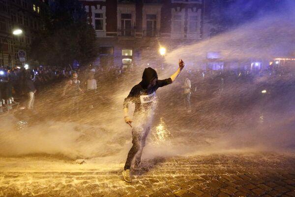 Один из демонстрантов, протестующих против саммита G20 в Гамбурге, пытается устоять на ногах во время разгона акции с применением водометов - Sputnik Грузия