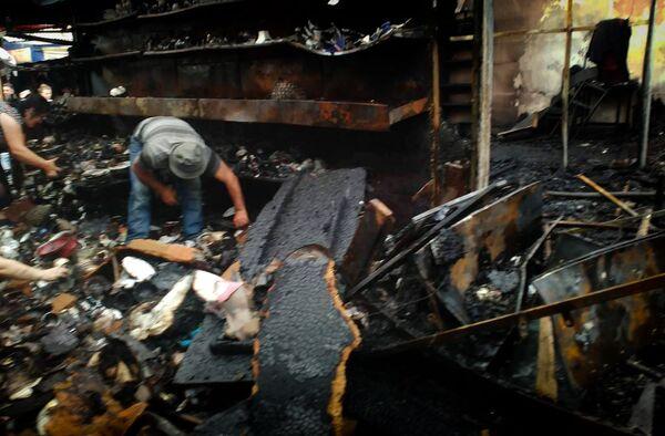 Работники торговых точек ищут уцелевший товар после пожара на вещевом рынке в Поти - Sputnik Грузия