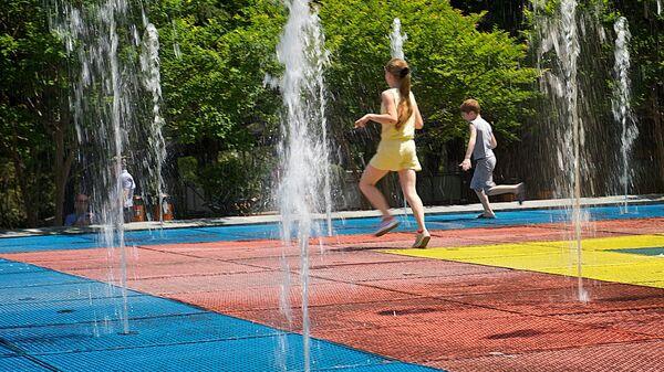 Дети бегают под струями фонтана в одном из тбилисских парков жарким летним днем - Sputnik Грузия