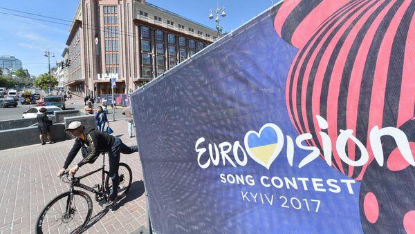 Человек едет на велосипеде мимо официального логотипа конкурса песни «Евровидение» в центре Киева - Sputnik Грузия