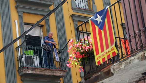 Мужчина развешивает одежду на балконе на севере Барселоны, на фоне флага Каталонии - Sputnik Грузия