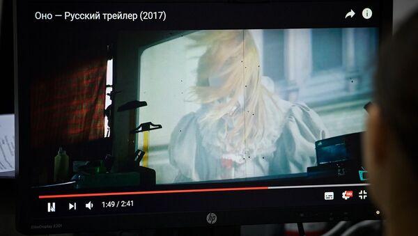 Девушка смотрит трейлер фильма Оно на экране компьютера - Sputnik Грузия