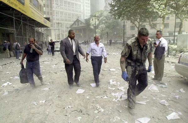 Шокированные люди в сопровождении полицейского бредут по улице, покрытой обломками башен Всемирного торгового центра 11 сентября 2001 года в Нью-Йорке - Sputnik Грузия