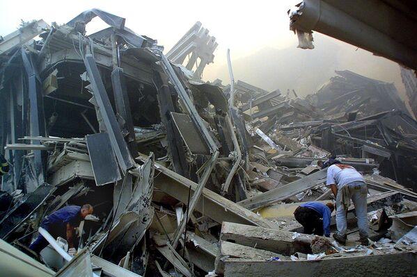 Спасатели в поисках выживших пробираются через обломки башен Всемирного торгового центра 11 сентября 2001 года в Нью-Йорке - Sputnik Грузия