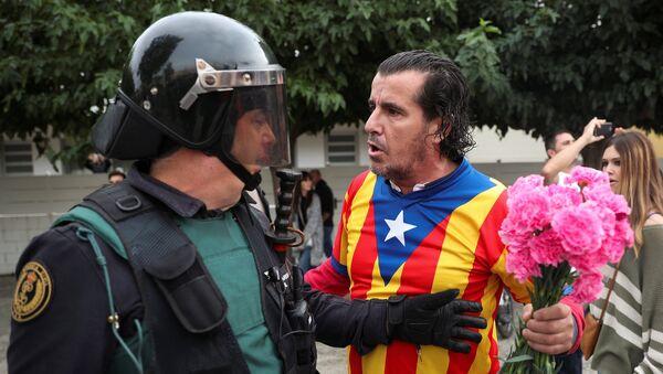 Человек, одетый в рубашку с каталонским флагом и держащий гвоздики, сталкивается с испанским офицером гражданской гвардии за пределами избирательного участка для референдума о независимости в Сант-Джулиа-де-Рамис - Sputnik Грузия