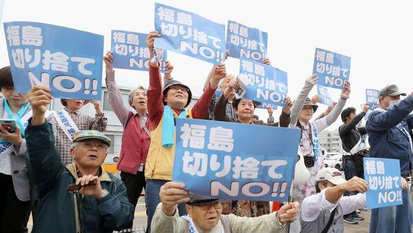 Истцы, которые подали в суд на TEPCO и японское правительство, демонстрируют плакаты перед окружным судом Фукусимы в Фукусиме, Япония - Sputnik Грузия
