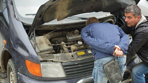 Водитель и механик пытаются починить автомобиль - Sputnik Грузия