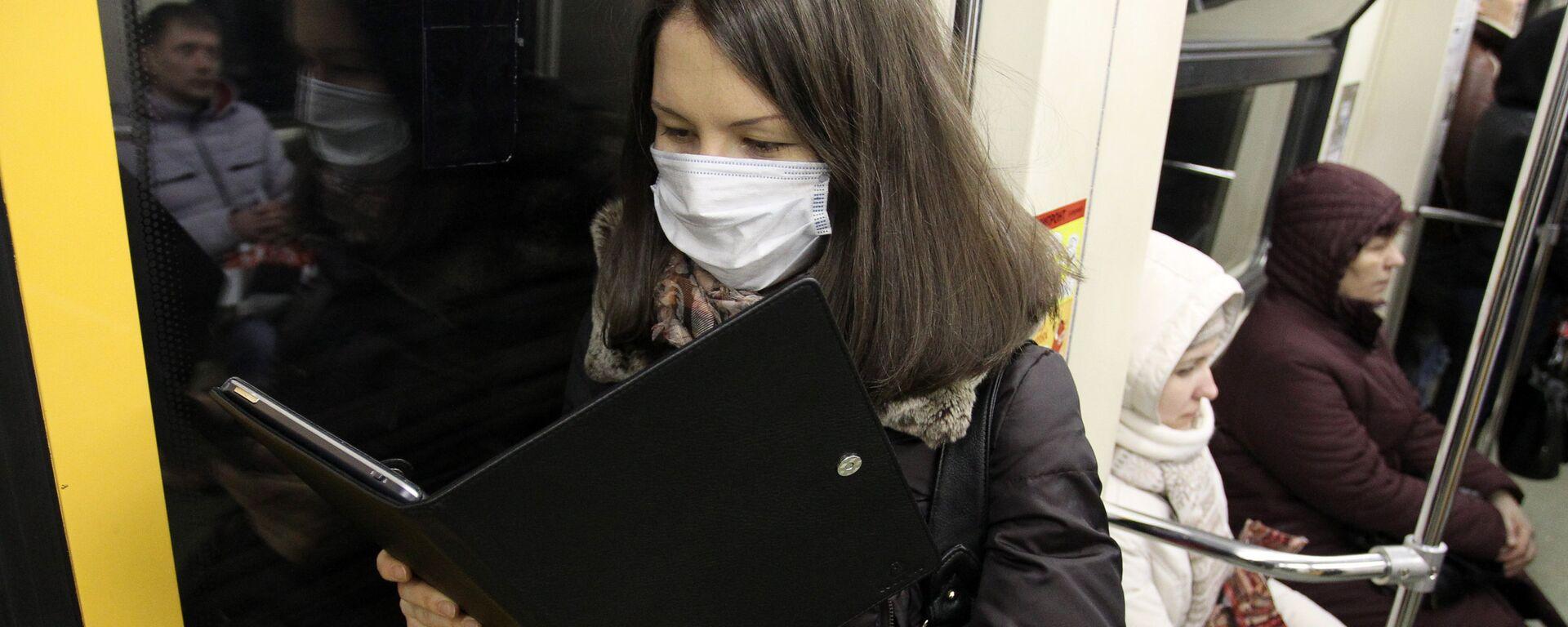 Девушка в защитной маске читает электронную книгу - Sputnik Грузия, 1920, 02.03.2021