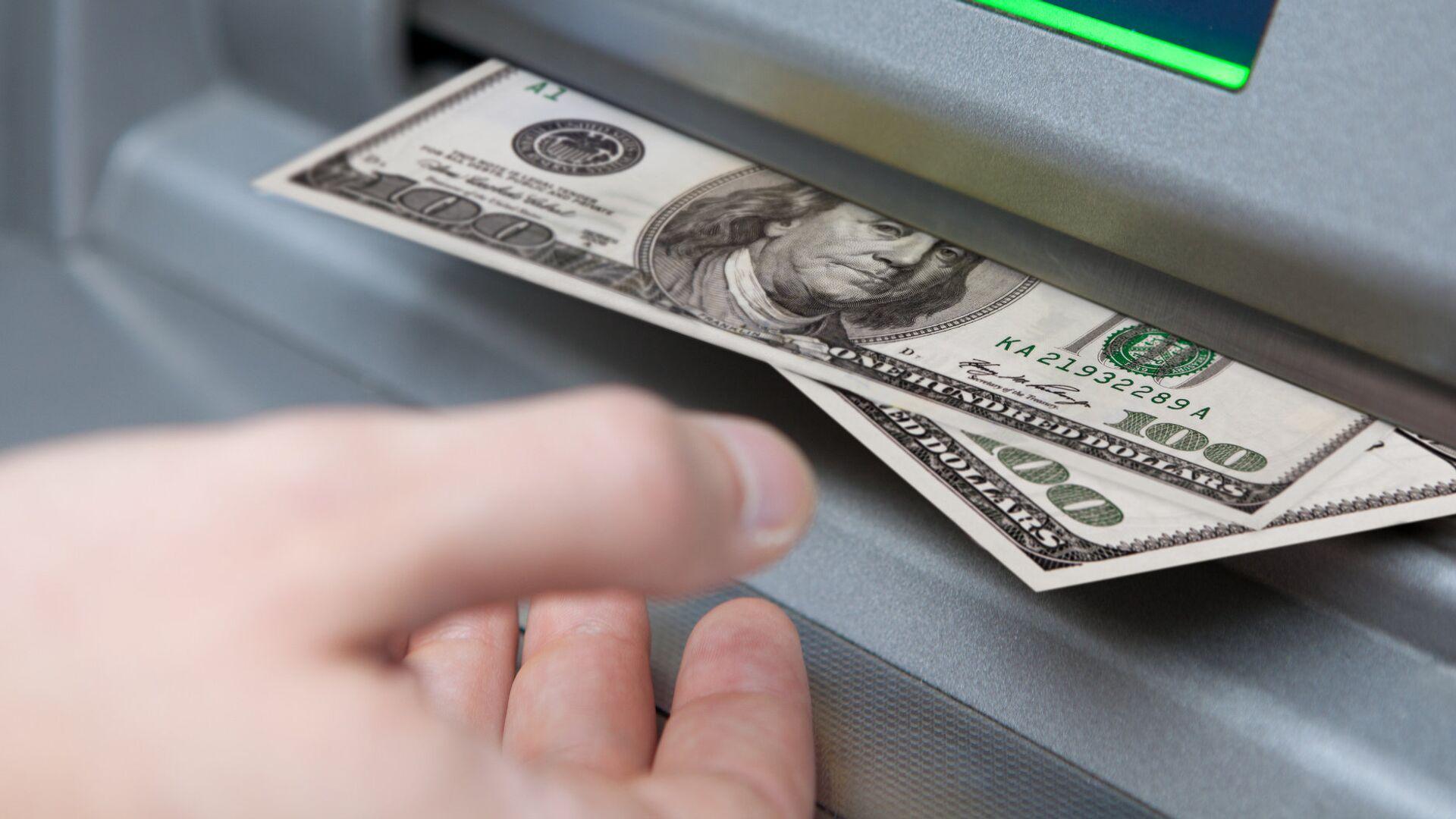 Мужчина берет купюры долларов из банкомата - Sputnik Грузия, 1920, 16.09.2021