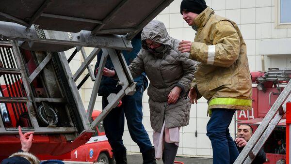 Сотрудники пожарной охраны МЧС помогают посетителям выбраться из торгового центра «Зимняя вишня» в Кемерово, где произошел пожар - Sputnik Грузия