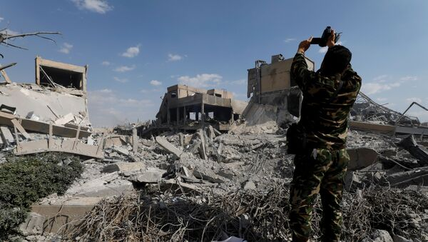 Солдат фотографирует разрушенный научно-исследовательский центр в Дамаске после бомардировки - Sputnik Грузия