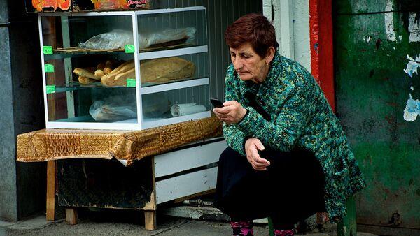 Женщина в хлебной лавке с мобильным телефоном - Sputnik Грузия