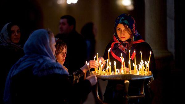 Верующие ставят свечки в церкви перед иконой Богородицы - Sputnik Грузия