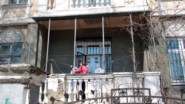 Центр города. Женщина развешивает белье на балконе старинной усадьбы. - Sputnik Грузия