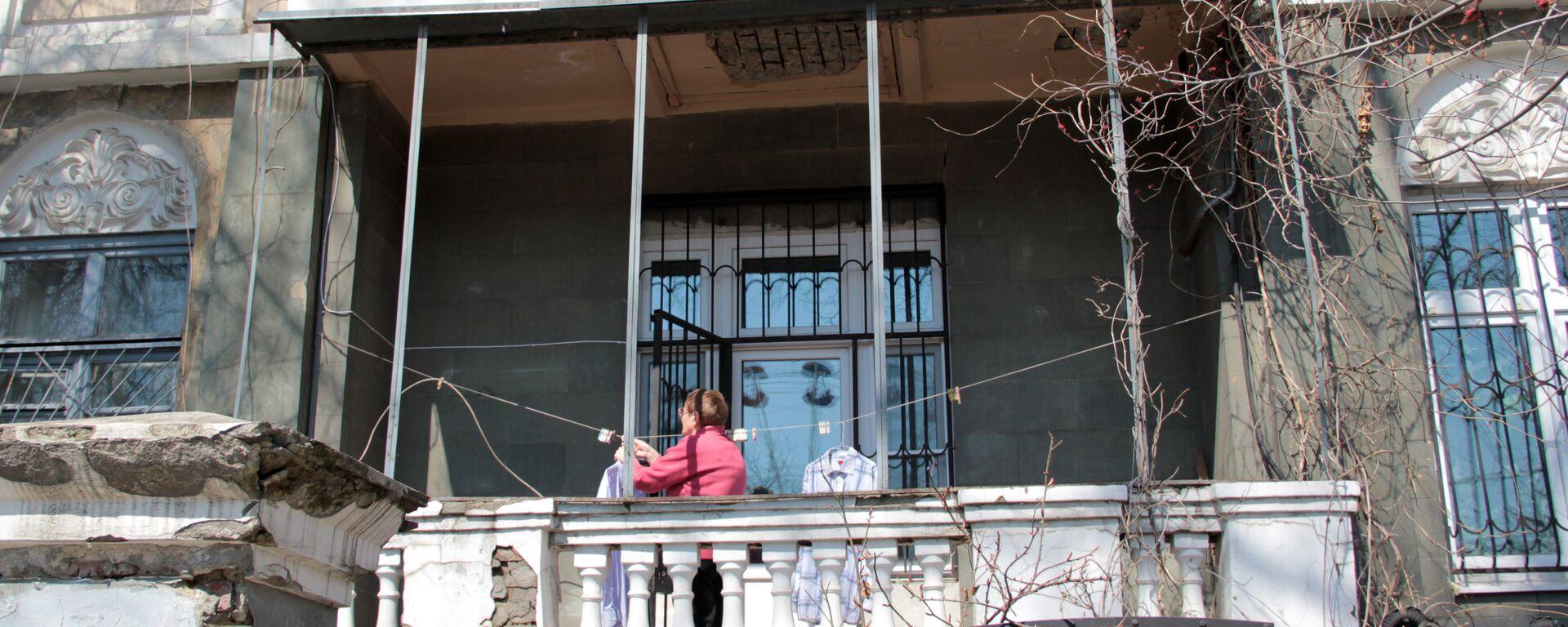 Центр города. Женщина развешивает белье на балконе старинной усадьбы. - Sputnik Грузия, 1920, 22.08.2021