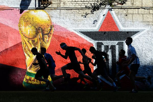 Игроки молодежного футбольного клуба во время разминки на футбольной площадке в  Санкт-Петербурге. Позади бегущих спортсменов красуется граффити с кубком чемпионата мира-2018 - Sputnik Грузия