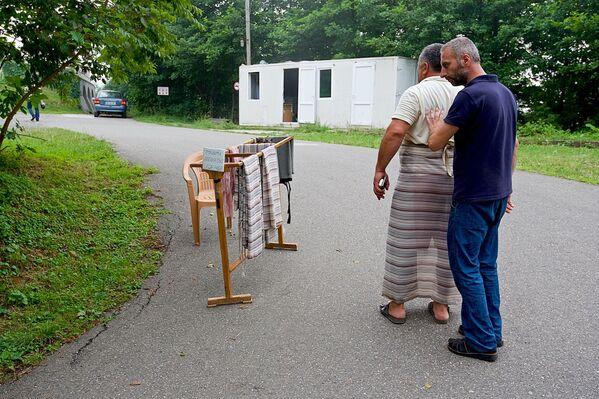Неподалеку от входа в храм посетителей встречает местный служитель, который помогает туристам обернуть ткань, прикрывающую ноги, если на них одеты шорты или мини-юбки. Женщинам также дают платки, чтобы они повязали их себе на голову - Sputnik Грузия