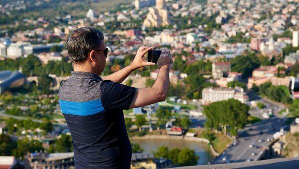 Турист фотографирует Тбилиси на смартфон  - Sputnik Грузия