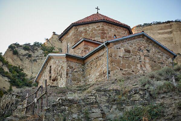 К монастырю из центра города Мцхета ведет тупиковая дорога. Ехать до монастыря примерно девять километров. На фото - храм Иоанна Крестителя, который был построен между 560 и 580 годами. Считается, что Святой Шио сам выбрал место для закладки храма - Sputnik Грузия