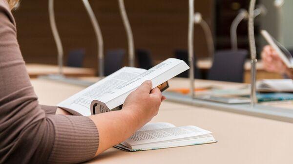 Девушка читает книгу в библиотеке - Sputnik Грузия