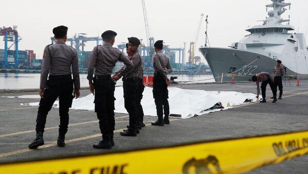 Оцепление из сотрудников полиции на берегу в порту Джакарты, куда доставляют находки с места крушения Боинга, Индонезия - Sputnik Грузия
