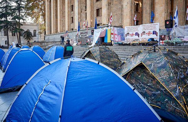 Часть палаток убрали, хотя половина из них еще находится у здания парламента. Там же неподалеку дежурят усиленные наряды полиции - Sputnik Грузия