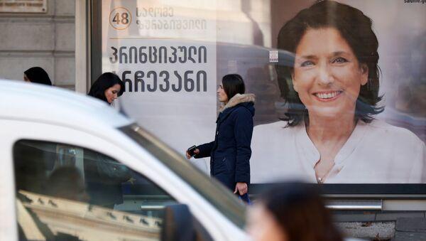 Люди на фоне предвыборного плаката Саломе Зурабишвили - Sputnik Грузия